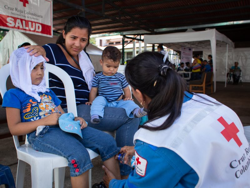 "A Colombian Red Cross volunteer pours water on Bianca's 5 year-old daughter's legs in an effort to bring her high fever down. Bianca often travels from San Cristobal into Cúcuta looking for basic medical assistance for her children and to sell basic goods to support her three children. ""There are no doctors or medicines in Venezuela"", she explains. ""The buildings are empty there"". Cúcuta, Colombia. Nov. 10, 2018. ©Erika Piñeros    **Note: Not for commercial use. Editorial use only. No Book Sales. Mandatory credit/byline. Not for sale for marketing or advertising campaigns. Image to be distributed exactly as supplied. No archive. All rights and copyright retained by photographer. No Syndication. No third-party distribution. Photo to be used only with the original story."