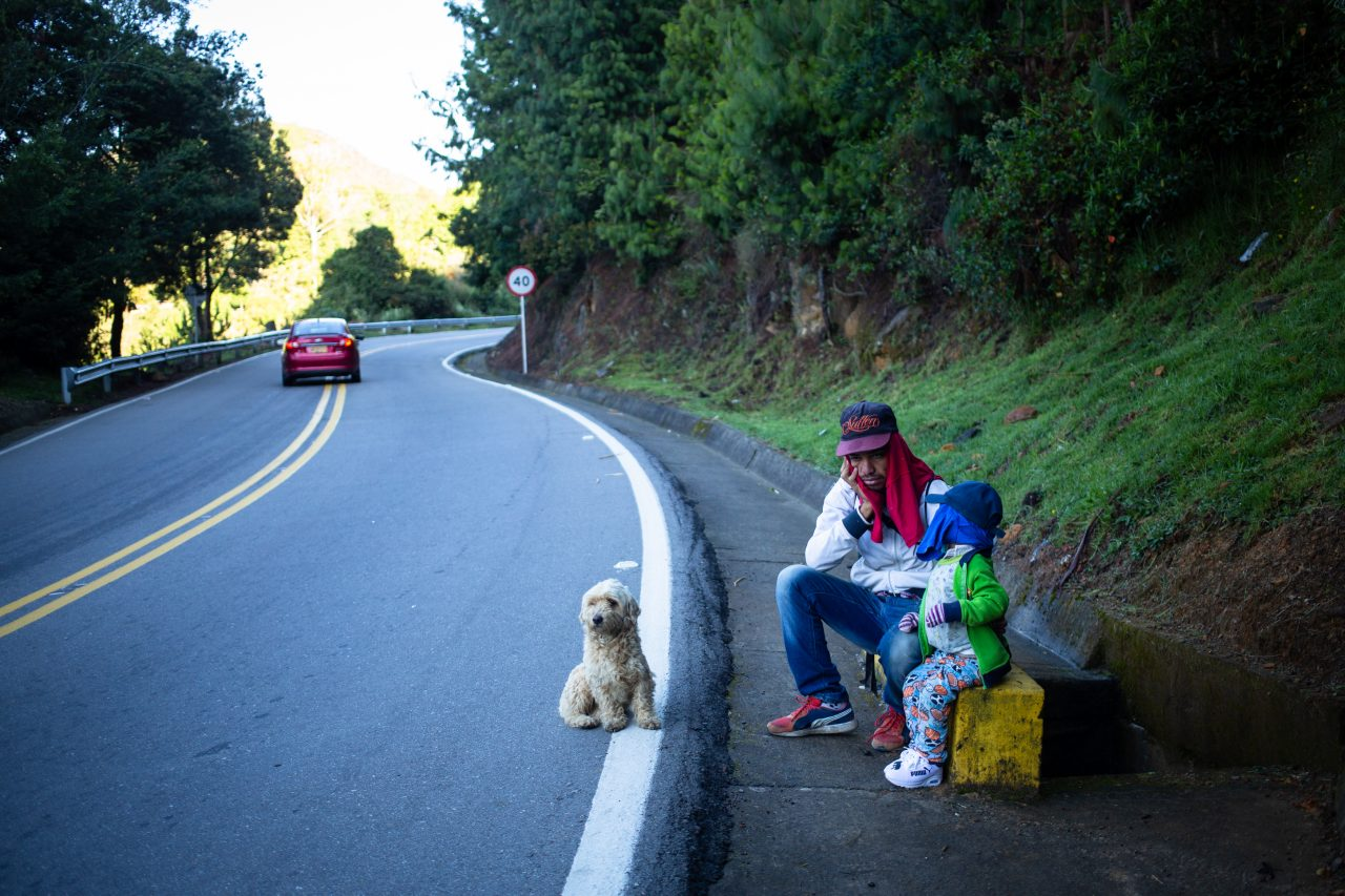 Juan, 28, and his son Santiago take a rest hoping to get a lift to take them across the paramo between Cúcuta and Bucaramanga. The highlands where temperatures drop down to 5-0 °C. Pamplona, Colombia. Nov. 12, 2018. ©Erika Piñeros    **Note: Not for commercial use. Editorial use only. No Book Sales. Mandatory credit/byline. Not for sale for marketing or advertising campaigns. Image to be distributed exactly as supplied. No archive. All rights and copyright retained by photographer. No Syndication. No third-party distribution. Photo to be used only with the original story.