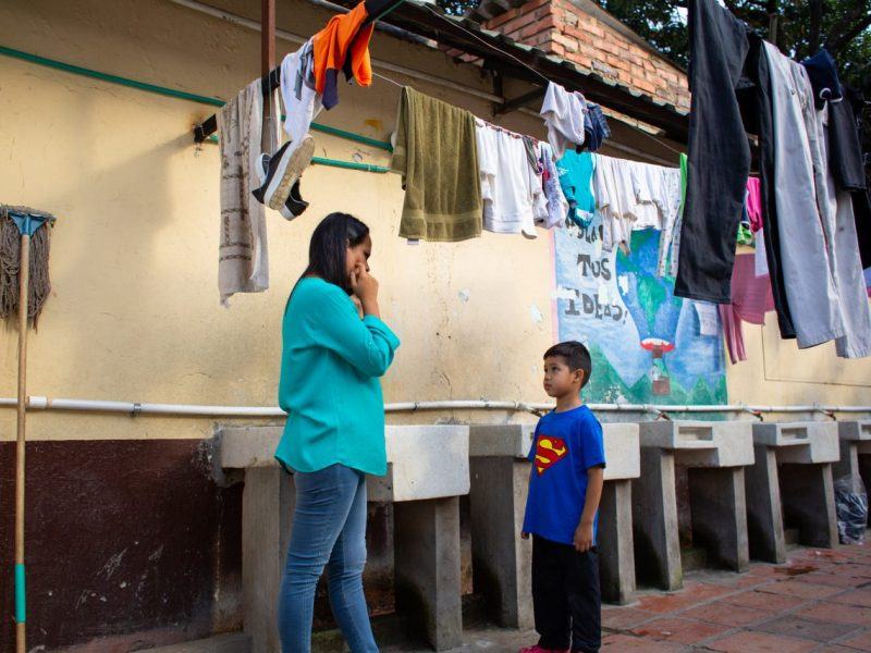 Emily García talks on the phone while her son, Samuel, who suffers a rare extreme type of epilepsy, stares at her at a shelter in Cúcuta. Emily decided to leave Venezuela and is in the process to claim asylum in Colombia on medical grounds. Cúcuta, Colombia. Nov. 10, 2018. ©Erika Piñeros