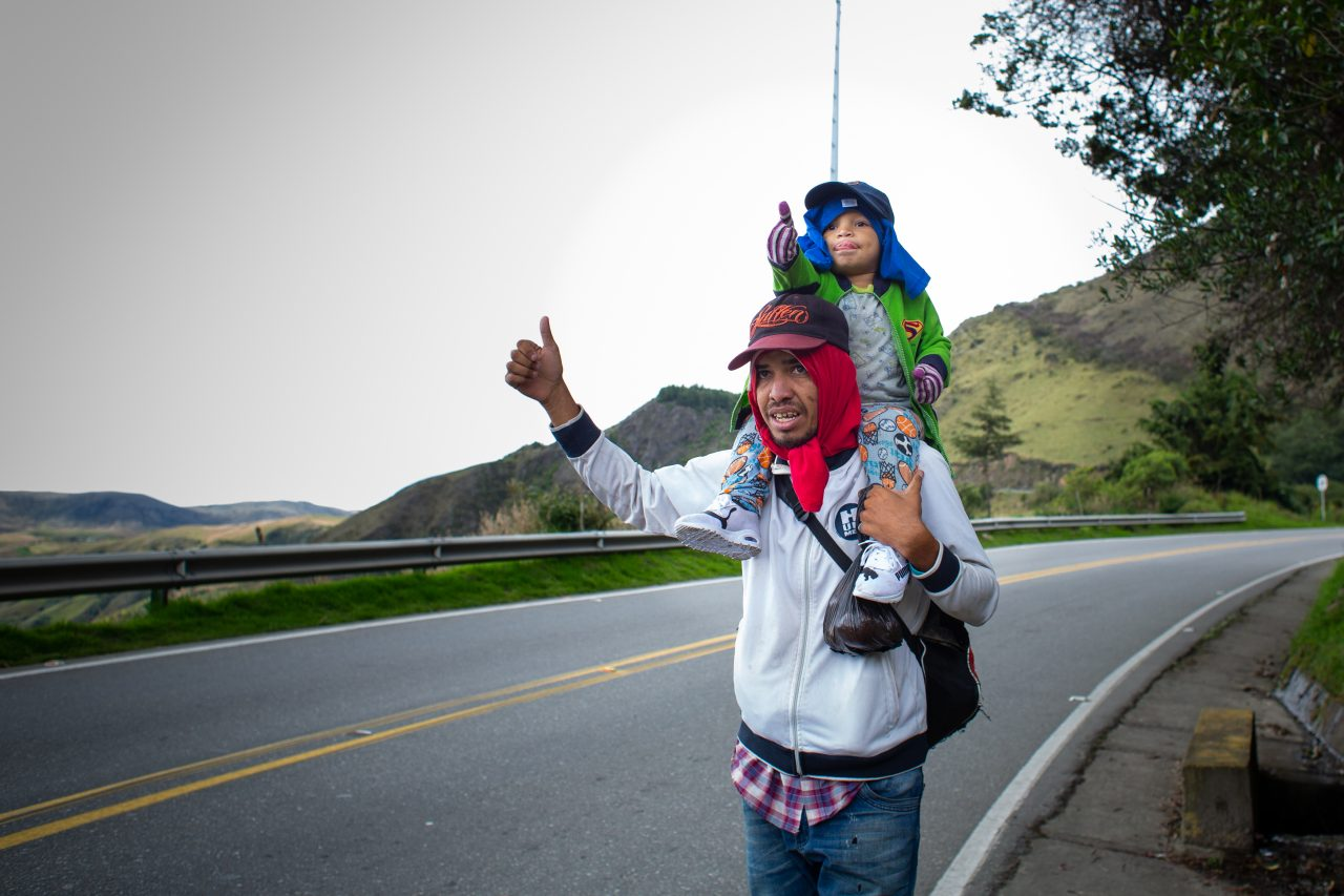 Santiago, 3 years-old, helps his father hitch a ride to help them cross the paramo between Cúcuta and Bucaramanga, where temperatures drop down to 5-0 °C. Pamplona, Colombia. Nov. 12, 2018. ©Erika Piñeros    **Note: Not for commercial use. Editorial use only. No Book Sales. Mandatory credit/byline. Not for sale for marketing or advertising campaigns. Image to be distributed exactly as supplied. No archive. All rights and copyright retained by photographer. No Syndication. No third-party distribution. Photo to be used only with the original story.